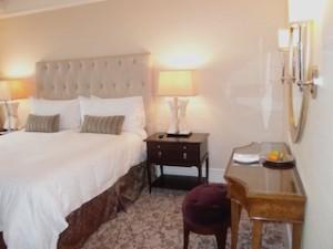 フォーシーズンズホテルシンガポール(シンガポール)の部屋のベッドとサイドテーブル